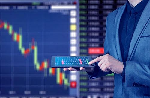inwestor z tabletem w ręce na tle tablicy z japońskimi świecami