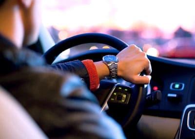kierowca za kierownicą z zegarkiem na ręce