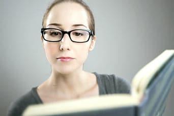 kobieta w okularach czytająca książkę