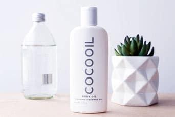 butelka cocooil body gel i butelka z przezroczystą cieczą i roślina w doniczce