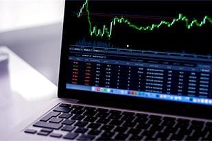 wykres cen akcji wyświetlony na ekranie laptopa