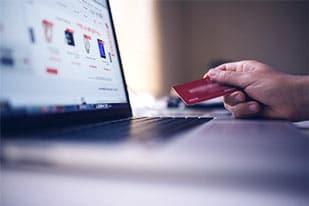 karta płatnicza i monitor w trakcie zakupów przez Internet