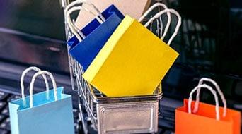 torby zakupowe postawione na laptopie