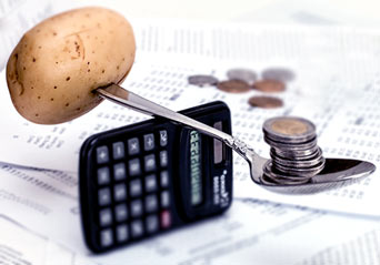 ziemniak na łyżce na kalkulatorze i pieniądze